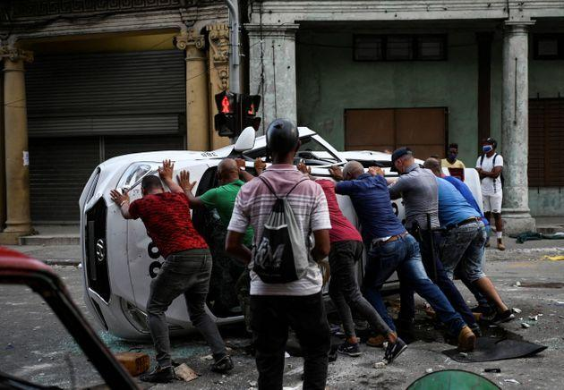 TOPSHOT - People push an overturned car in the street in the framework of a demonstration against Cuban President Miguel Diaz-Canel in Havana, on July 11, 2021. - Thousands of Cubans took part in rare protests Sunday against the communist government, marching through a town chanting