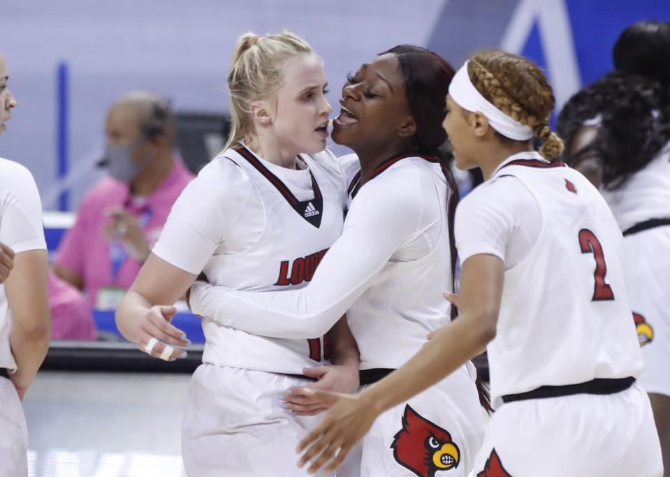 Louisville's Dana Evans, center, celebrates with Hailey Van Lith, left, and Ahlana Smith, right, during the second half of Louisville's 65-53 victory over Wake Forest in the quarterfinals of the Atlantic Coast Conference NCAA women's college basketball game in Greensboro, N.C., Friday, March 5, 2021. (Ethan Hyman/The News & Observer via AP)