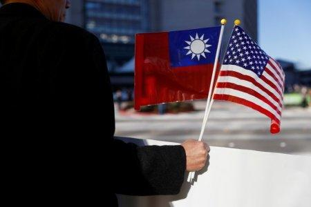 FILE PHOTO - A demonstrator holds flags of Taiwan and the United States in support of Taiwanese President Tsai Ing-wen during an stop-over after her visit to Latin America in Burlingame, California, U.S., January 14, 2017. REUTERS/Stephen Lam