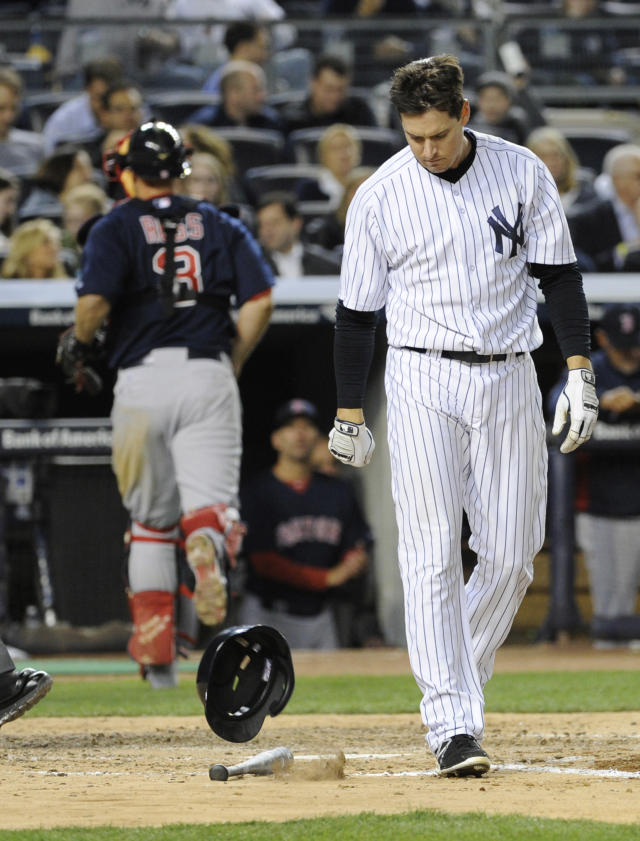 New York Yankees batter Kelly Johnson reacts after striking out to end the fifth inning of a baseball game as Boston Red Sox catcher David Ross, left, heads for the dugout Friday, April 11, 2014, at Yankee Stadium in New York. (AP Photo/Bill Kostroun)