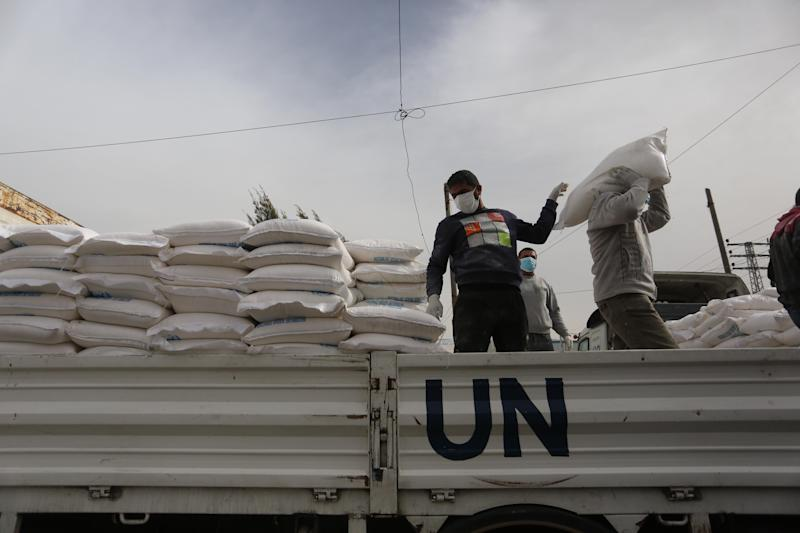 Palestinian employees at the U.N. Relief and Works Agency for Palestinian Refugees prepare food aid rations that will be delivered to people's homes due to the COVID-19 pandemic. (Photo: Majdi Fathi/NurPhoto via Getty Images)