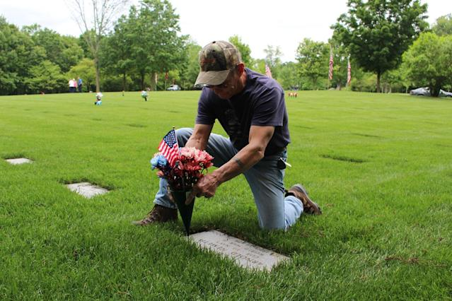 <p>Vietnam-era Marine veteran Jim Segletes of Easton, Pa., places flowers on the grave of his father-in-law, a World War II veteran who died in 2000, at Indiantown Gap National Cemetery in Annville, Pa. on May 27, 2017. (Photo:Michael Rubinkam/AP) </p>