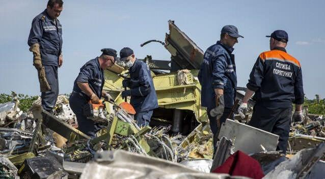 Ukrainian rescue servicemen inspect part of the wreckage of Malaysia Airlines flight MH17. Photo: Rob Stothard/Getty