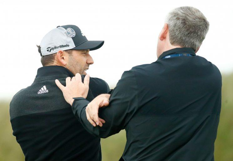 Sergio Garcia gets medical attention after slamming his club on Friday. (Getty Images)