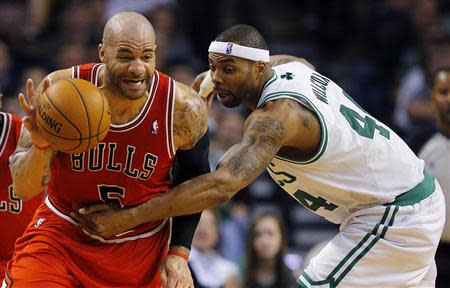 Chicago Bulls forward Carlos Boozer (L) is fouled by Boston Celtics forward Chris Wilcox in the second half of their NBA basketball game in Boston, Massachusetts February 13, 2013. REUTERS/Brian Snyder