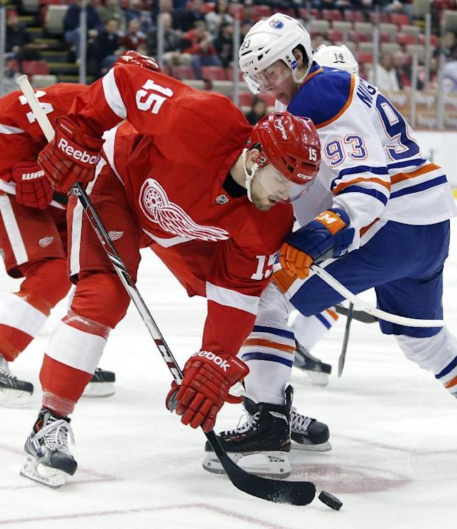 Detroit Red Wings' Riley Sheahan (15) wins the faceoff against Edmonton Oilers' Ryan Nugent-Hopkins (93) during the first period of an NHL hockey game Friday, March 14, 2014, in Detroit. (AP Photo/Duane Burleson)