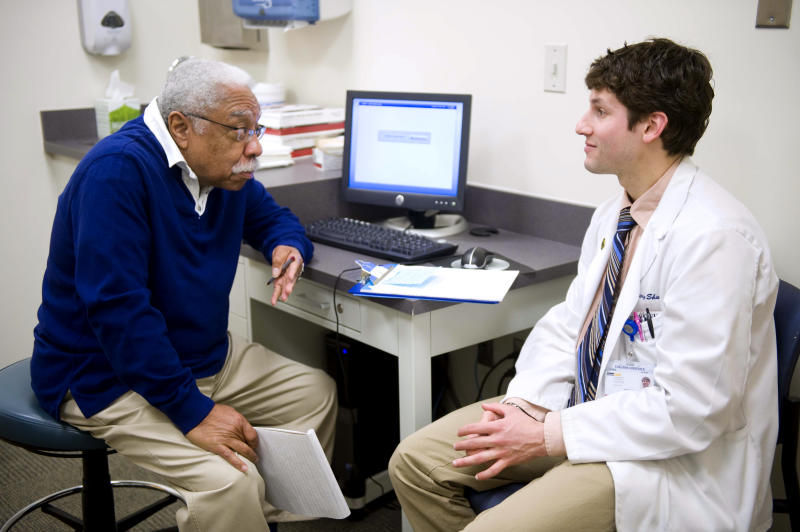 John Askew, Sr., a patient/actor, left gives feedback to third-year Georgetown medical student Gregory Shumer after a training session in an examining room on the Georgetown Medical School campus in Washington, Friday, March 16, 2012. As the nation moves to paperless medicine, doctors are grappling with an awkward challenge: How do they tap the promise of computers, smartphones and iPads in the exam room without losing the human connection with their patients? Are the gadgets a boon, or a distraction? (AP Photo/Kevin Wolf)