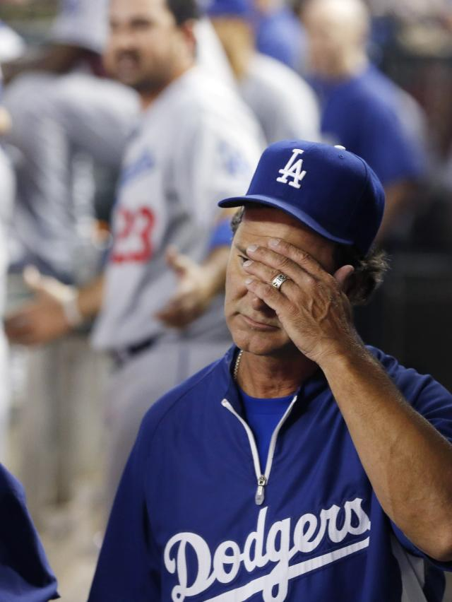 Los Angeles Dodgers manager Don Mattingly, right, covers his face after Adrian Gonzalez (23) is ejected for arguing a call in the sixth inning during a baseball game against the Arizona Diamondbacks on Wednesday, Sept. 18, 2013, in Phoenix. (AP Photo/Ross D. Franklin)
