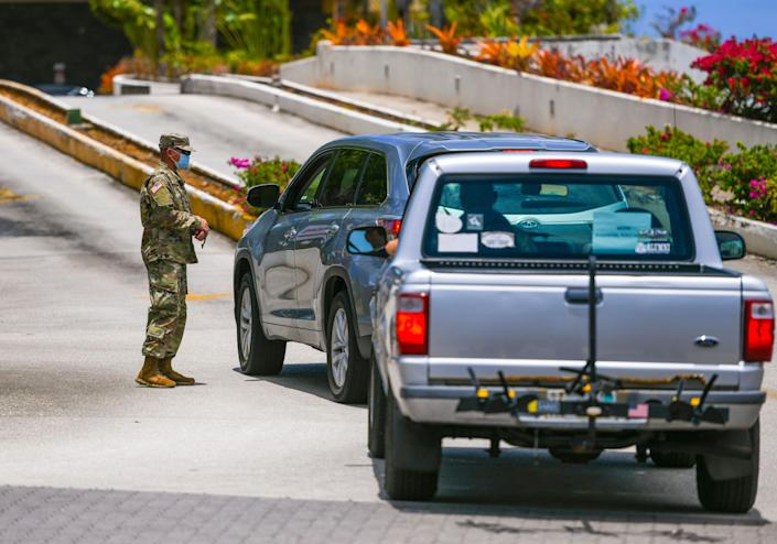 Drivers are stopped by a Guam National Guard soldier at a security checkpoint posted at the driveway entrance to the Pacific Star Resort & Spa in Tumon on Thursday, April 9, 2020. Hotels on island that normally cater to the island's tourism industry, were used to isolate some of the 5,000 military personnel who serve aboard the U.S.S. Theodore Roosevelt.