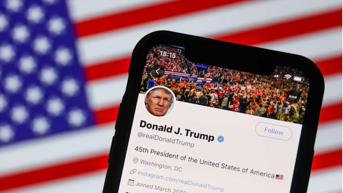 An illustration photo of Mr Trump's Twitter feed with American flag in background