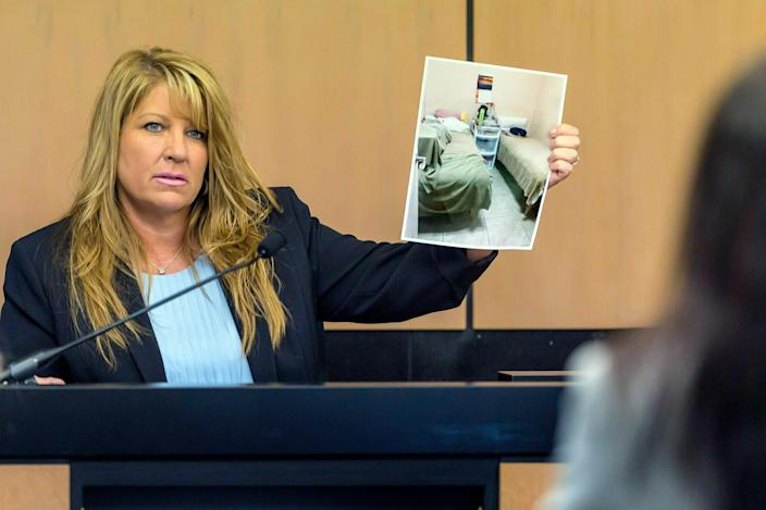 Karen Herzog, a Florida Department of Health inspector, shows a photo she took of beds in a room during her inspection of Orchids of Asia Day Spa, during a motion hearing in the Robert Kraft prostitution solicitation case in West Palm Beach, Florida.