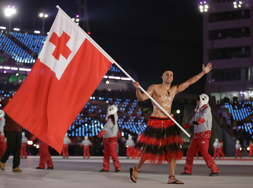 <p>Pita Taufatofua carries the flag of Tonga during the opening ceremony of the 2018 Winter Olympics in Pyeongchang, South Korea, Friday, Feb. 9, 2018. (AP Photo/Vadim Ghirda) </p>