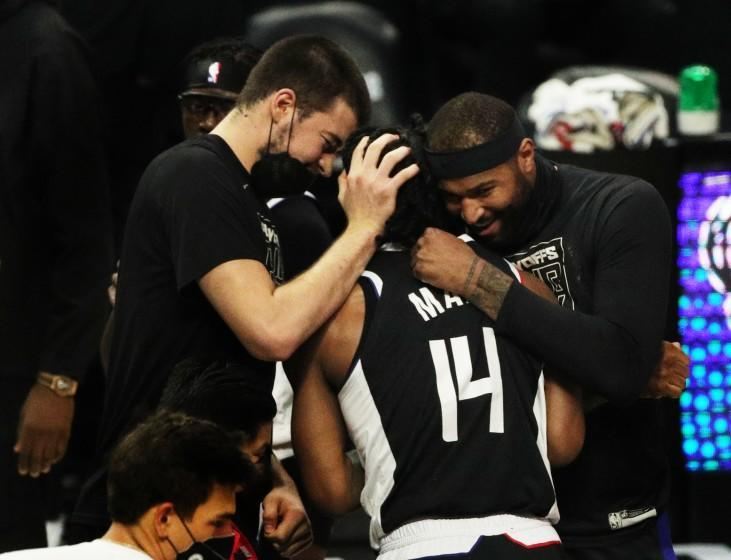 LOS ANGELES, CA - JUNE 18, 2021: Teammates hug high-scorer LA Clippers guard Terance Mann (14) during a timeout as the Clippers beat the Utah Jazz to advance to the Western Conference NBA Playoffs at Staples Center on June 18, 2021 in Los Angeles, California.(Gina Ferazzi / Los Angeles Times)