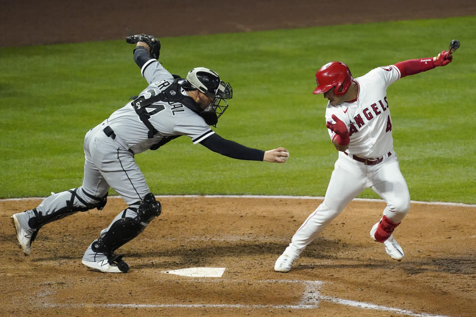 Los Angeles Angels shortstop Jose Iglesias (4) avoids a tag attempt by Chicago White Sox catcher Yasmani Grandal (24) during the fourth inning of an MLB baseball game Friday, April 2, 2021, in Anaheim, Calif. Iglesias was out at first. (AP Photo/Ashley Landis)