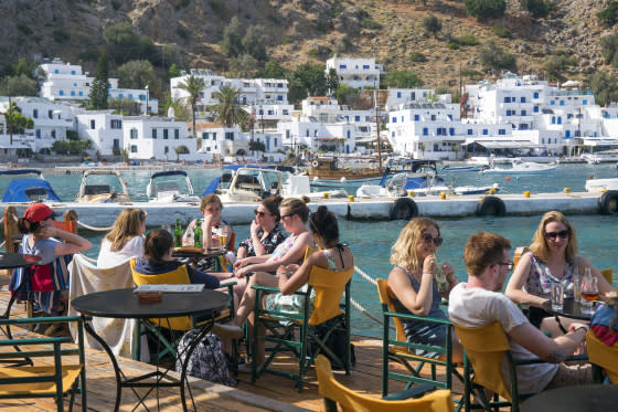 Young people relaxing on waterfront cafe terrace beside the harbor in the town of Loutro.