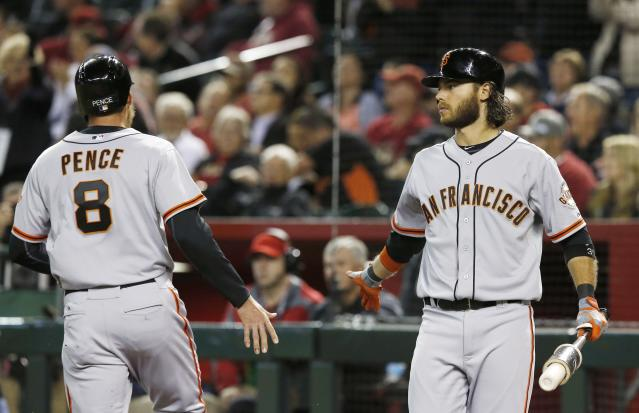 San Francisco Giants' Hunter Pence (8) celebrates after scoring against the Arizona Diamondbacks, with teammate Brandon Crawford during the sixth inning of a baseball game, Wednesday, April 2, 2014, in Phoenix. (AP Photo/Ross D. Franklin)