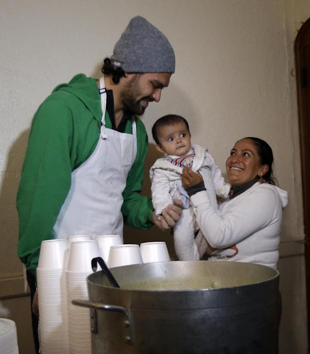 New York Jets NFL football quarterback Mark Sanchez, left, talks to Yolanda Chimborazo, right, and 6-month-old Ailyn Saeteros during a visit to the Community Soup Kitchen of Morristown as part of the team's Thanksgiving Day week celebration, Tuesday, Nov. 26, 2013, in Morristown, N.J. (AP Photo/Julio Cortez)