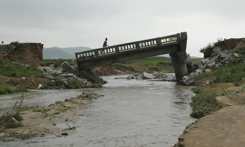 In this July 30, 2012 photo, a man walks over a damaged bridge after heavy rain in Onchon County, North Korea. The rain Sunday and Monday followed downpours earlier this month that killed nearly 90 people and left more than 60,000 homeless, officials said. The floods also come on the heels of a severe drought, fueling renewed food worries about a country that already struggles to feed its people. (AP Photo/Jon Chol Jin)