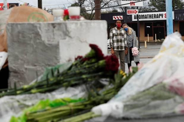 Anthony Roberts, 33, and Olivia Roberts, 28, pause before laying flowers on Thursday, at a makeshift memorial outside Gold Spa following deadly shootings in the Atlanta area on Tuesday.