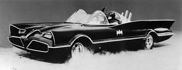 <p>Adam West, in full Batman costume, drives the original Batmobile, which is really a 1955 Lincoln Futura concept car weighing nearly three tons. (Photo: Bettmann/Getty Images) </p>