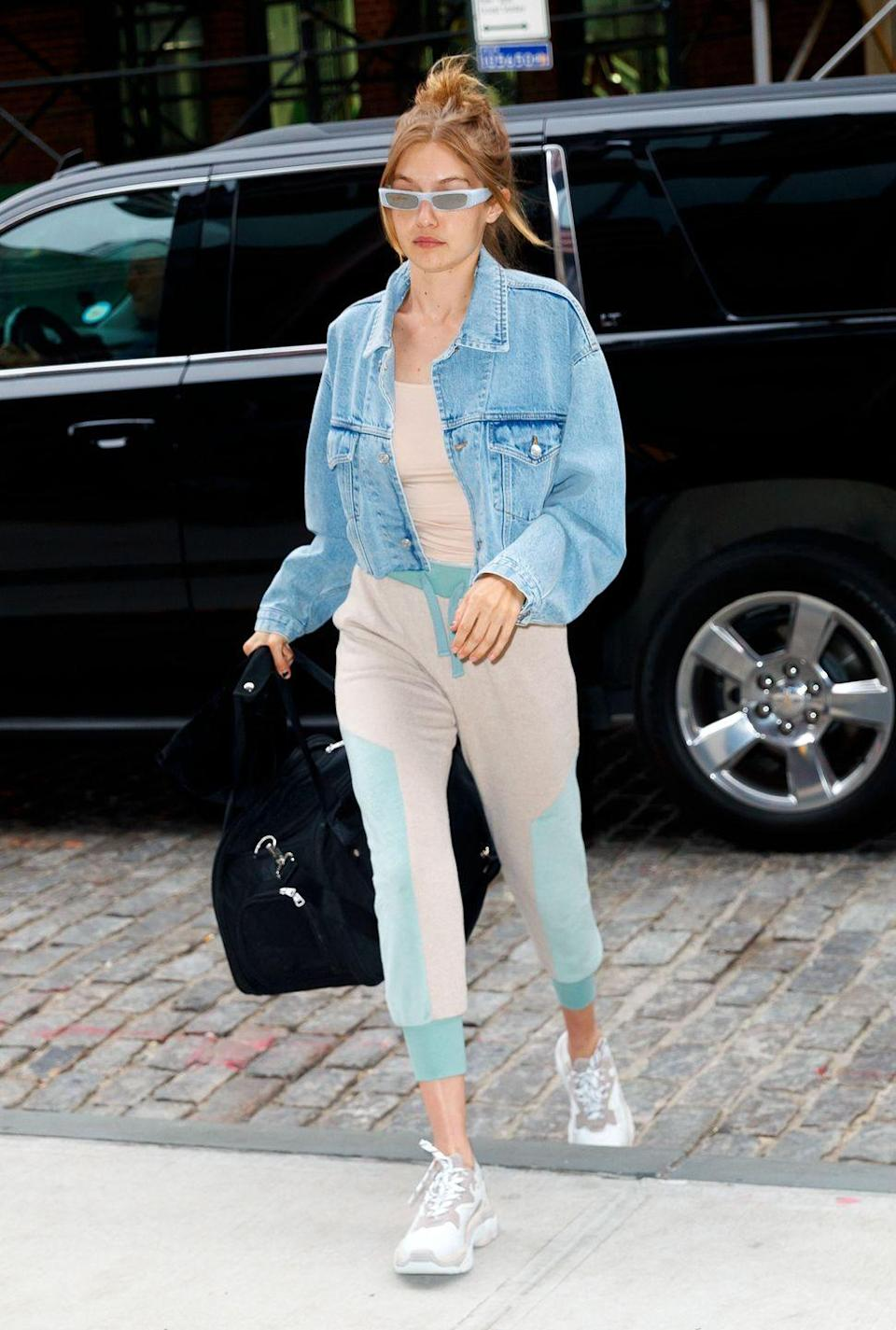 <p>In a casual nude athleisure set, denim jacket and baby blue sunglasses arriving home in NYC. </p>