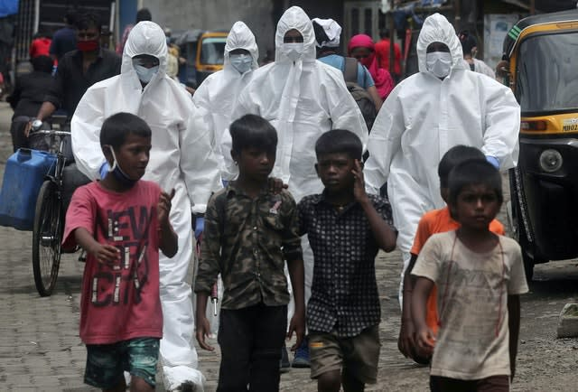 Health workers wearing protective clothing arrive to screen people for Covid-19 symptoms at a slum in Mumbai, India