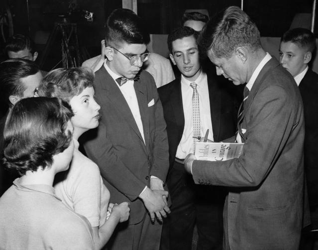 "<p>Sen. John F. Kennedy signs a copy of his book ""Profiles in Courage"" for a young fan, circa 1956-1957. (Photo: John F. Kennedy Presidential Library and Museum) </p>"