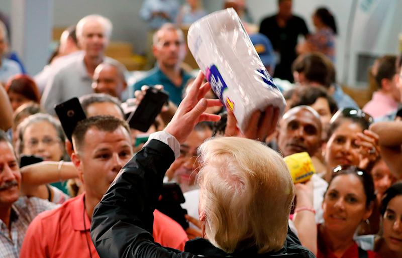 President Donald Trump throws rolls of paper towels to a crowd of local residents affected by Hurricane Maria as he visits a disaster relief distribution center Tuesday in San Juan, Puerto Rico.