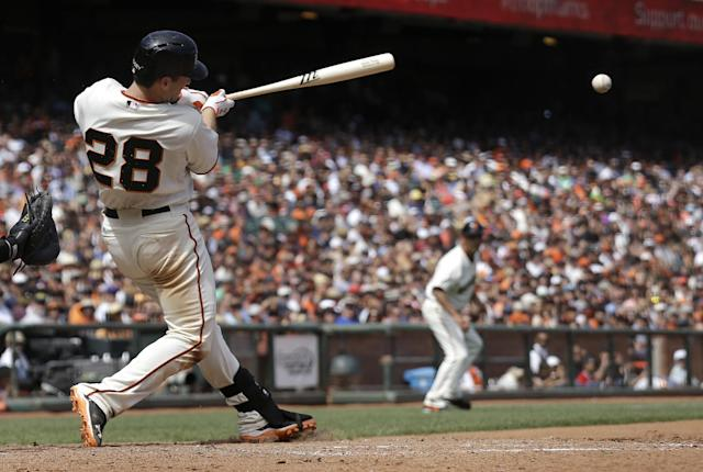 San Francisco Giants' Buster Posey (28) hits a single to score Angel Pagan during the seventh inning of a baseball game against the Chicago White Sox in San Francisco, Wednesday, Aug. 13, 2014. (AP Photo/Jeff Chiu)