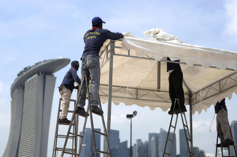In this photo taken Feb. 6, 2014, migrant workers from India set up a canopy for an event with a backdrop of the Central Business District skyline, in Singapore. One of the wealthiest countries in the world, Singapore has about 1.1 million foreign workers out of a population of 5.3 million. The vast majority of them are low wage workers from developing countries - mainly from India, China and Bangladesh. (AP Photo/Joseph Nair)