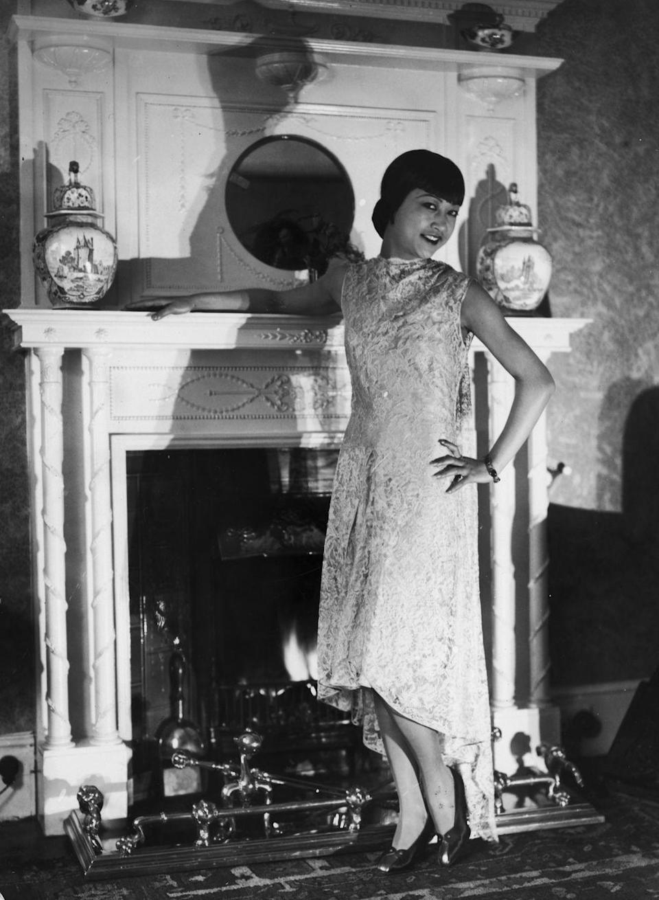 """<p>Chinese-American film star Anna May Wong poses for the camera in front of a grand fireplace in her London apartment. The actress, who became a fixture on-screen in the '20s, <a href=""""https://www.notablebiographies.com/We-Z/Wong-Anna-May.html"""" rel=""""nofollow noopener"""" target=""""_blank"""" data-ylk=""""slk:moved to London"""" class=""""link rapid-noclick-resp"""">moved to London</a> after becoming frustrated with the type of roles she was receiving in Hollywood. </p>"""