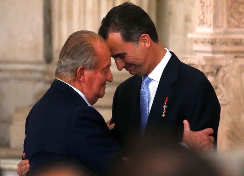FILE PHOTO: Spain's King Juan Carlos and his son Crown Prince Felipe attend the signature ceremony of the act of abdication at the Royal Palace in Madrid