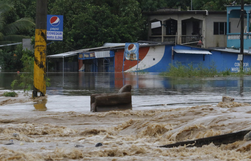 A chair sits in a flooded road after the passing of Iota in La Lima, Honduras, Wednesday, Nov. 18, 2020. Iota flooded stretches of Honduras still underwater from Hurricane Eta, after it hit Nicaragua Monday evening as a Category 4 hurricane and weakened as it moved across Central America, dissipating over El Salvador early Wednesday. (AP Photo/Delmer Martinez)