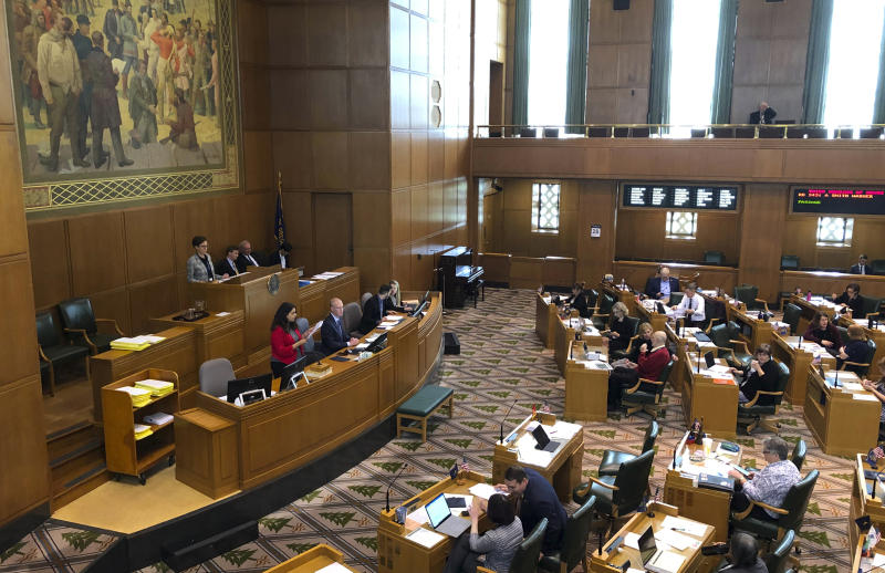 Lacy Ramirez Gruss, the reading clerk in the Oregon House of Representatives, at left in red jacket, reads a bill in its entirety on the House floor at the Capitol in Salem, Ore., on Tuesday, May 28, 2019. Republicans, who are in the minority in the House, have insisted since April 30 that bills be read in their entirety, not just by their summaries as is customary, in order to slow down business and try to wrest concessions from Democrats. (AP Photo/Andrew Selsky)