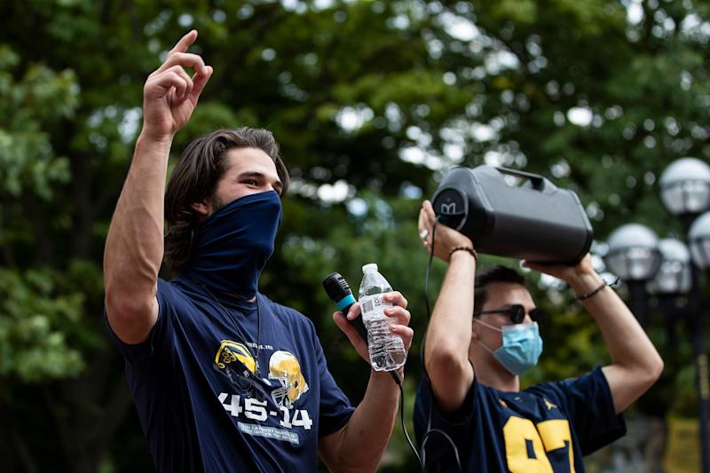 """U-M quarterback Dylan McCaffrey leads the singing of Michigan fight song """"Hail to the Victors"""" outside of Hatcher Graduate Library on the U-M campus in Ann Arbor on Sept. 5, 2020. U-M football players' parents, supporters and some players and coaches march from Michigan Stadium to the central campus to protest the postponement of the fall football season."""