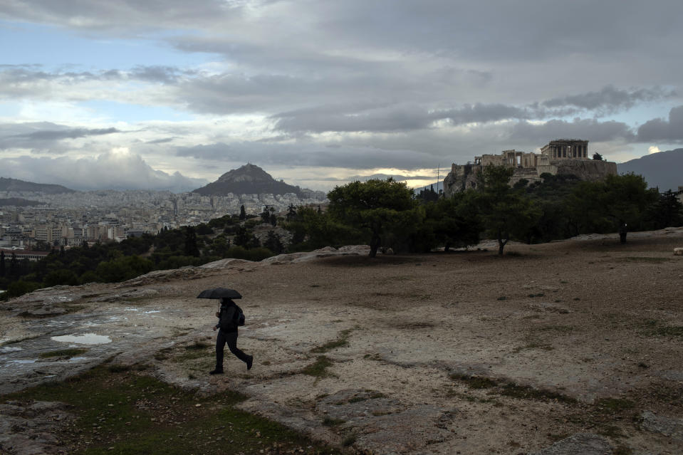 A man with an umbrella walks during a rainfall on Pnyx hill in front the ancient Acropolis hill, with the ruins of the fifth century BC Parthenon temple, in Athens, on Monday, Nov. 30, 2020 Greek officials say the number of new infections is waning in most parts of the country, which has been in lockdown for three weeks.(AP Photo/Petros Giannakouris)