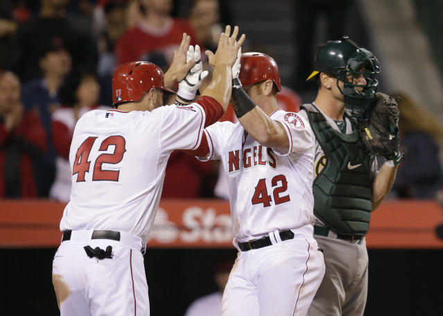 Los Angeles Angels' Kole Calhoun, center, celebrates his two-run home run with Chris Iannetta, left, as Oakland Athletics catcher John Jaso stands near home plate during the fourth inning of a baseball game Tuesday, April 15, 2014, in Anaheim, Calif. (AP Photo/Jae C. Hong)