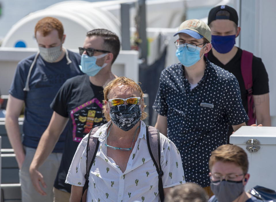Passengers wear face masks on a Halifax Transit ferry as it arrives in Dartmouth, N.S. on Friday, July 24, 2020, the first day they have been mandatory on public transit. Masks will become mandatory in most indoor public places in Nova Scotia on Friday and the province's health minister says it will be up to the public to carry out its responsibility to wear them. THE CANADIAN PRESS/Andrew Vaughan