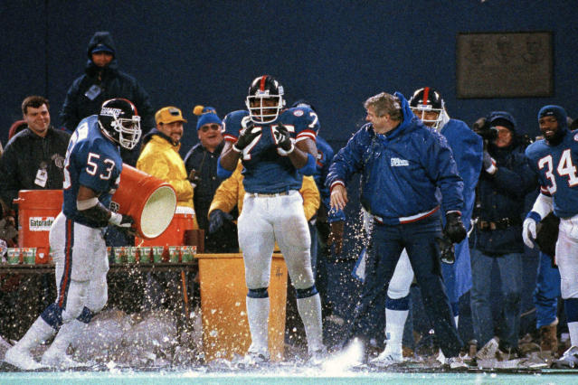 FILE - In this Jan. 11, 1987, file photo, New York Giants George Martin (75) watches as teammate Harry Carson empties the water bucket on coach Bill Parcells during the last minute of their 17-0 win over the Washington Redskins in the NFC championship in East Rutherford, N.J. Teams are never supposed to choose to kick off after winning the coin toss because it means they won't get the ball to start either half. But games rarely have wind gusts of 25 mph and beyond. That was the case when the Giants beat the Redskins 17-0 for the 1986 NFC title. (AP Photo/Elise Amendola, File)