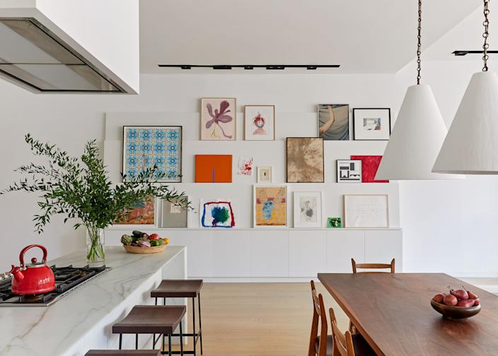 """<div class=""""caption""""> """"We began with a blank slate and worked with what was there, adding millwork to visually and functionally define spaces within the main living area,"""" says Bergin. In the dining room, a custom table by <a href=""""http://patrickkeesey.com/"""" rel=""""nofollow noopener"""" target=""""_blank"""" data-ylk=""""slk:Patrick Keesey"""" class=""""link rapid-noclick-resp"""">Patrick Keesey</a> is paired with chairs by Guillerme et Chambron and plaster pendants by <a href=""""https://www.roseuniacke.com/"""" rel=""""nofollow noopener"""" target=""""_blank"""" data-ylk=""""slk:Rose Uniacke"""" class=""""link rapid-noclick-resp"""">Rose Uniacke</a>. The shelf ledges highlight art by Beverly Buchanan, Emily Sundblad, and Patricia Iglesias. </div>"""