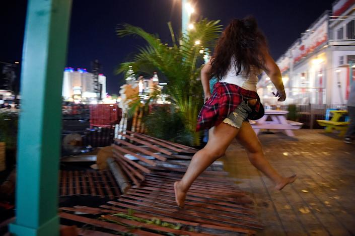 A person runs barefoot from the shooting.