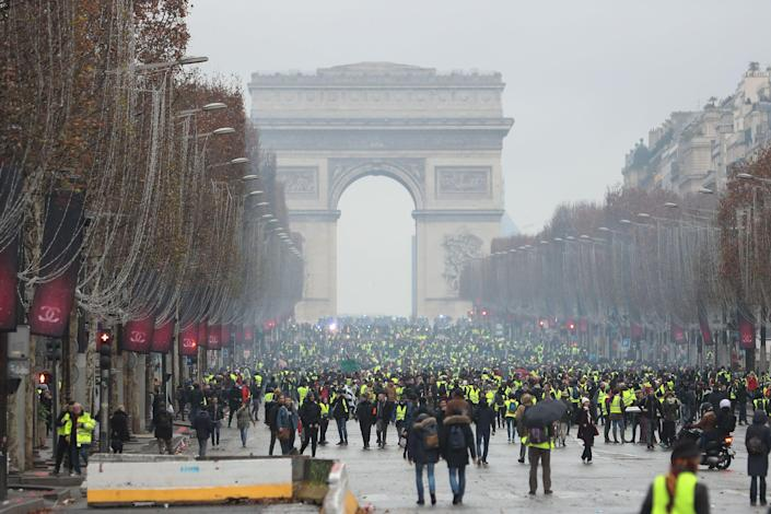 Protestors wearing yellow vests (Gilets jaunes) stand on the Champs Elysees avenue in Paris on Dec. 8, 2018 during a protest against rising costs of living they blame on high taxes. (Photo: Zakaria AbdelKafi/AFPGetty Images)