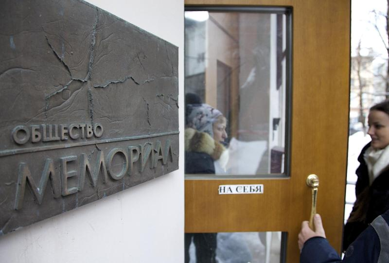 People talk near the entrance to human rights group Memorial's office, in Moscow, Russia, on Thursday, March 21, 2013, as prosecutors search for documents pertaining to all of its activities. The media arrived at the offices after social media alerted them to the search, but were not able to witness the search happening. Russian prosecutors are searching the offices of Memorial, one of the country's oldest and most respected rights nongovernmental organizations NGOs, which used to be funded from the U.S. Agency for International Development USAID, but funding dried up after Russia kicked USAID out of the country last year. (AP Photo/Ivan Sekretarev)