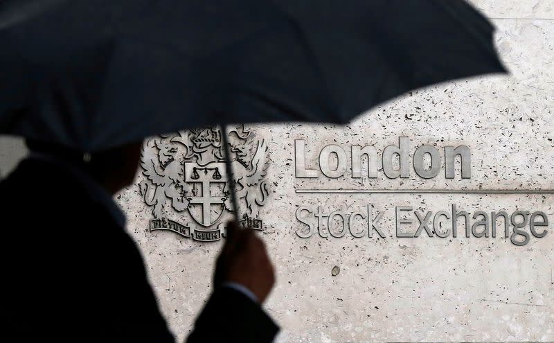 FILE PHOTO: FILE PHOTO: A man shelters under an umbrella as he walks past the London Stock Exchange
