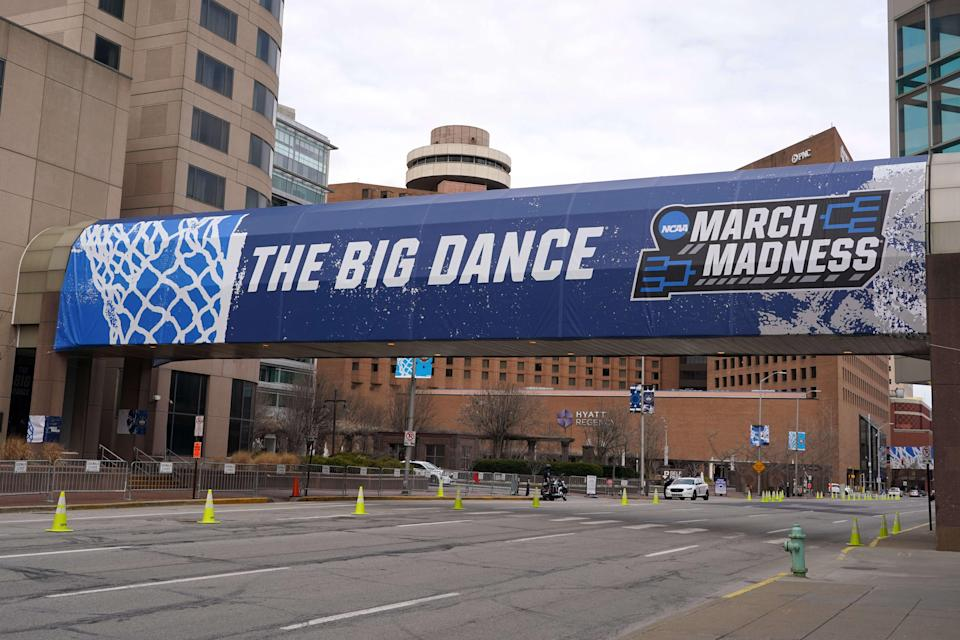 March Madness signage announces the men's NCAA Tournament at the Indiana Convention Center over mostly empty streets.