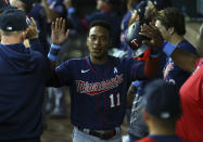 Minnesota Twins Jorge Polanco (11) is greeted in the dugout after scoring on a hit in the third inning against the Texas Rangers at a baseball game Sunday, June 20, 2021, in Arlington, Texas. (AP Photo/Richard W. Rodriguez)