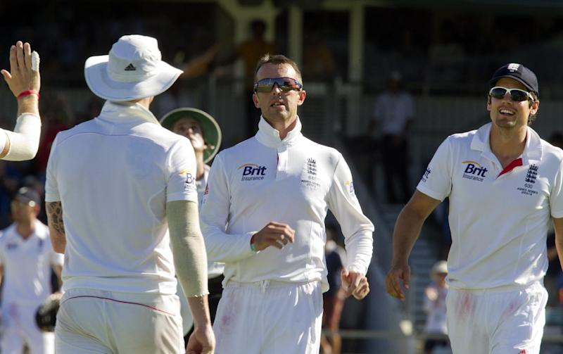 England spin bowler Graeme Swann (hatless) is congratulated by teamates for dismissing Australian opening batsman David Warner on the third day of the third Ashes cricket Test match in Perth on December 15, 2013