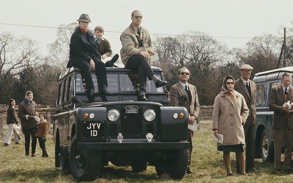 Members of the Royal family, including the Queen standing with Henry Somerset, 10th Duke of Beaufort, beside a Land Rover Series IIA station wagon with Princess Anne, Prince Philip and Prince Andrew - Popperfoto