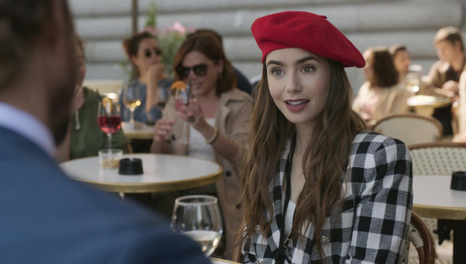 """This image released by Netflix shows Lily Collins in a scene from the series """"Emily in Paris."""" The program was nominated for an Emmy Award for outstanding comedy series. (Netflix via AP)"""