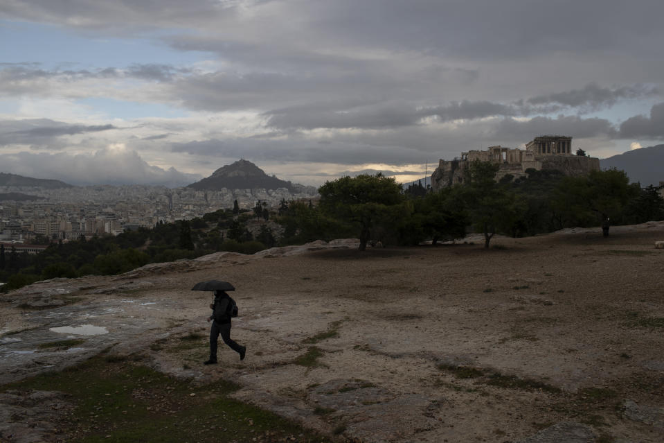 A man with an umbrella walks in the rain on Pnyx hill in front the ancient Acropolis hill, with the ruins of the fifth century BC Parthenon temple, in Athens, on Monday, Nov. 30, 2020 Greek officials say the number of new infections is waning in most parts of the country, which has been in lockdown for weeks.(AP Photo/Petros Giannakouris)